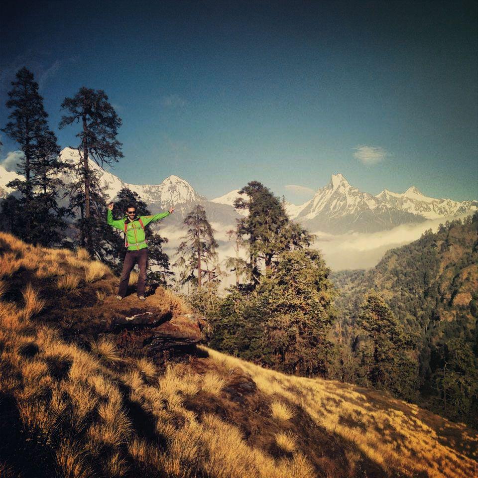 Mann steht auf Berg mit Bergen im Hintergrund.