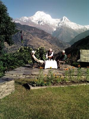 3 Personen sitzen in einer komfortablen Unterkunft in Nepal, im Hintergrund der Mt. Everest