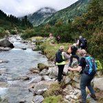 Gruppe von Wanderer ausgerüstet mit gutem Schuhwerk, Rucksack und Trekkingstöcken gehen dem Fluss entlang in ein Tal