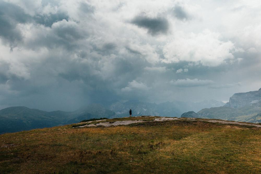 wolkenverhangener Himmel über offener Fläche, Berge im Hintergrund