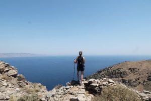 Wanderin steht auf Felsvorsprung über dem tiefblauen Meer, blauer Himmel