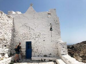 Weißes Mauerwerk einer Kirche, eine Person links von der kleinen blauen Tür
