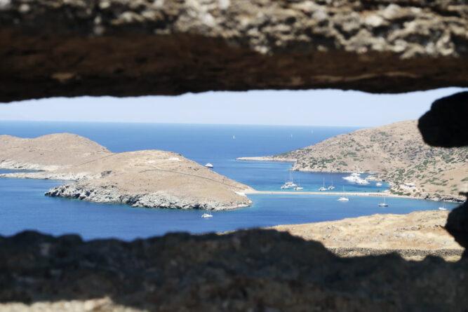 Perspektive durch Felsen hindurch, Blick auf felsige Bucht mit blauem Meer