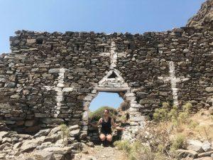 Grobes Mauerwerk mit Kreuzzeichnung. Eine Person in einem Torbogen
