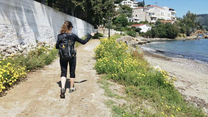 Wanderin auf einem Pfad am Meer, mit dem Finger zeigt sie nach vorne