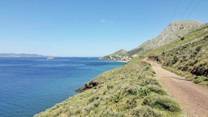 Breiter Weg in grüner Fläche, hügelig, blaues Meer zur Linken
