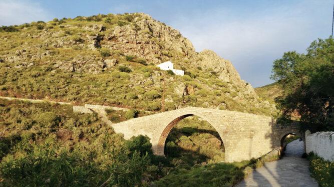 Steinerner Brückenbau. Steiniger Hügel mit weißem Häusschen darin