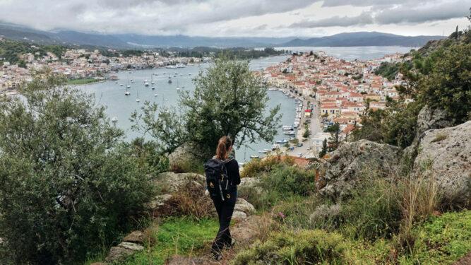 Wanderin steht auf einer Anhöhe mit Aussicht auf eine Stadt an einer Küste, bewölktes Wetter