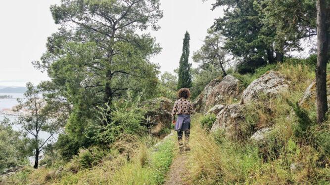 Wanderin auf schmalem Wanderpfad in einem Wald
