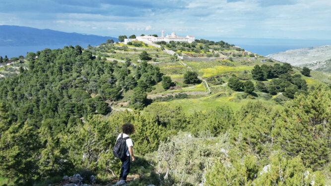 Weißes Klostergebäude in der Ferne auf einem grünen Hügel. Wanderin blick darauf.