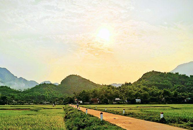 Sonne hinter leichten Wolken über hellgrünen Hügeln