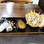 Verschiedene Speisen auf einem Teller; Frühlingsrollen, Soße und Salat