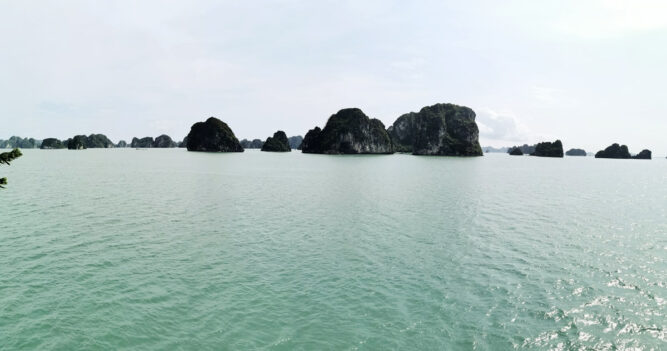 Grünliches Wasser in einer großen Bucht, dunkle Felsen im Wasser