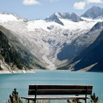 Aussicht auf eine Bank am See. Im Hintergrund schneebedeckte Berge