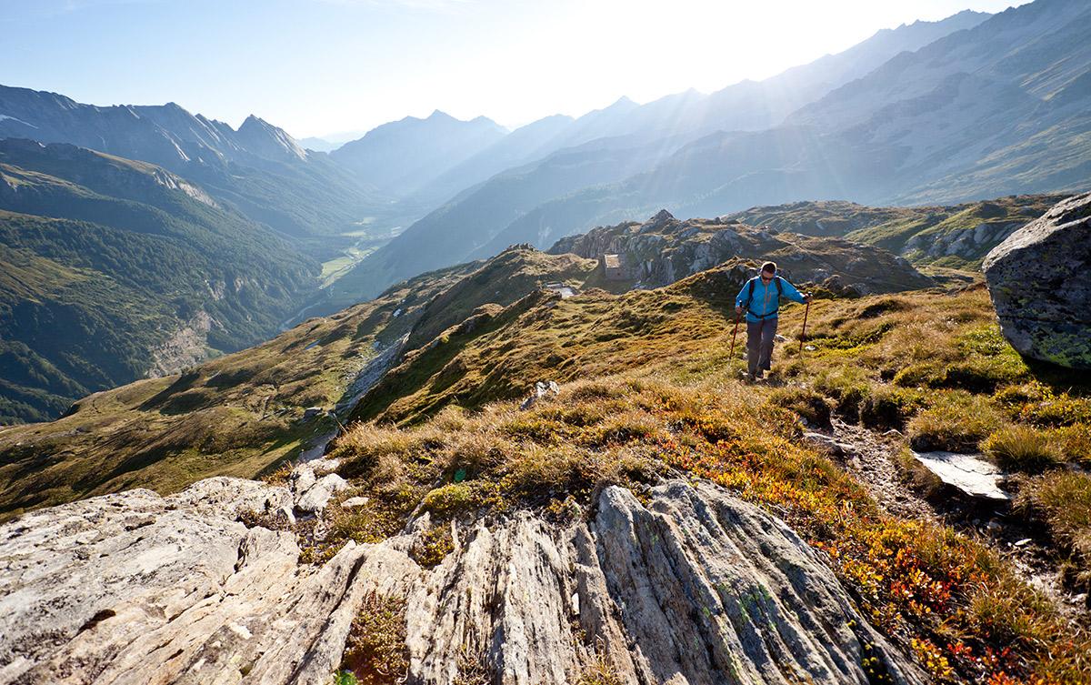 Wanderer auf alpiner Wiese. Sonnenstrahlen leuchten von hinten