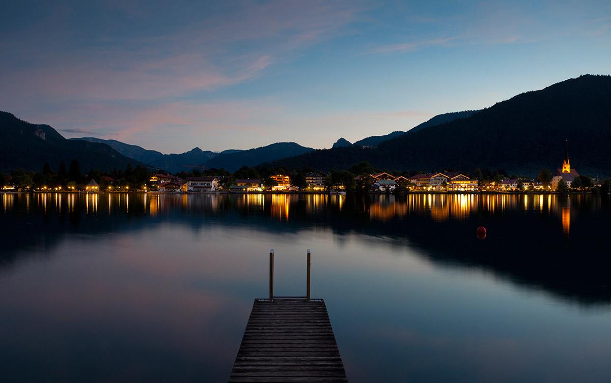 Ein See mit beleuchteten Häusern im Hintergrund bei Nacht