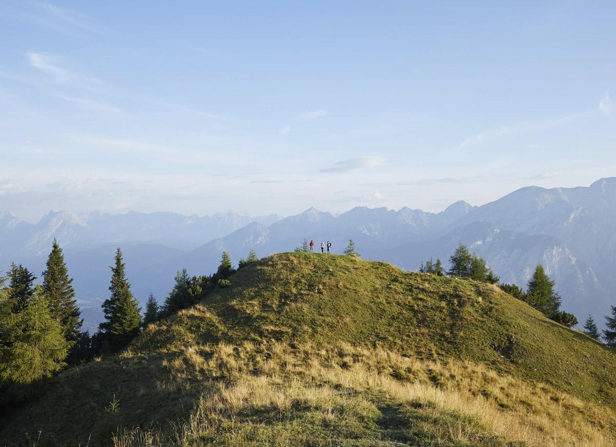 grüner hügel, drei menschen aus der ferne, berge im hintergrund