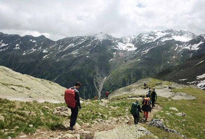 Mehrere Wanderer auf einem Pfad in den Alpen, wolkenverhangener Himmel