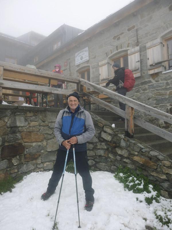 Mann mit Trekkingausrüstung vor Hütte, nebelig