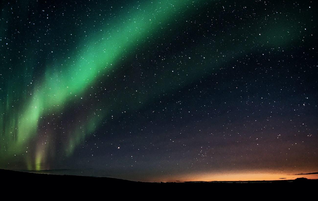 Nachthimmel mit Sternen und grünem Streifen, am Horizont oranger Himmel