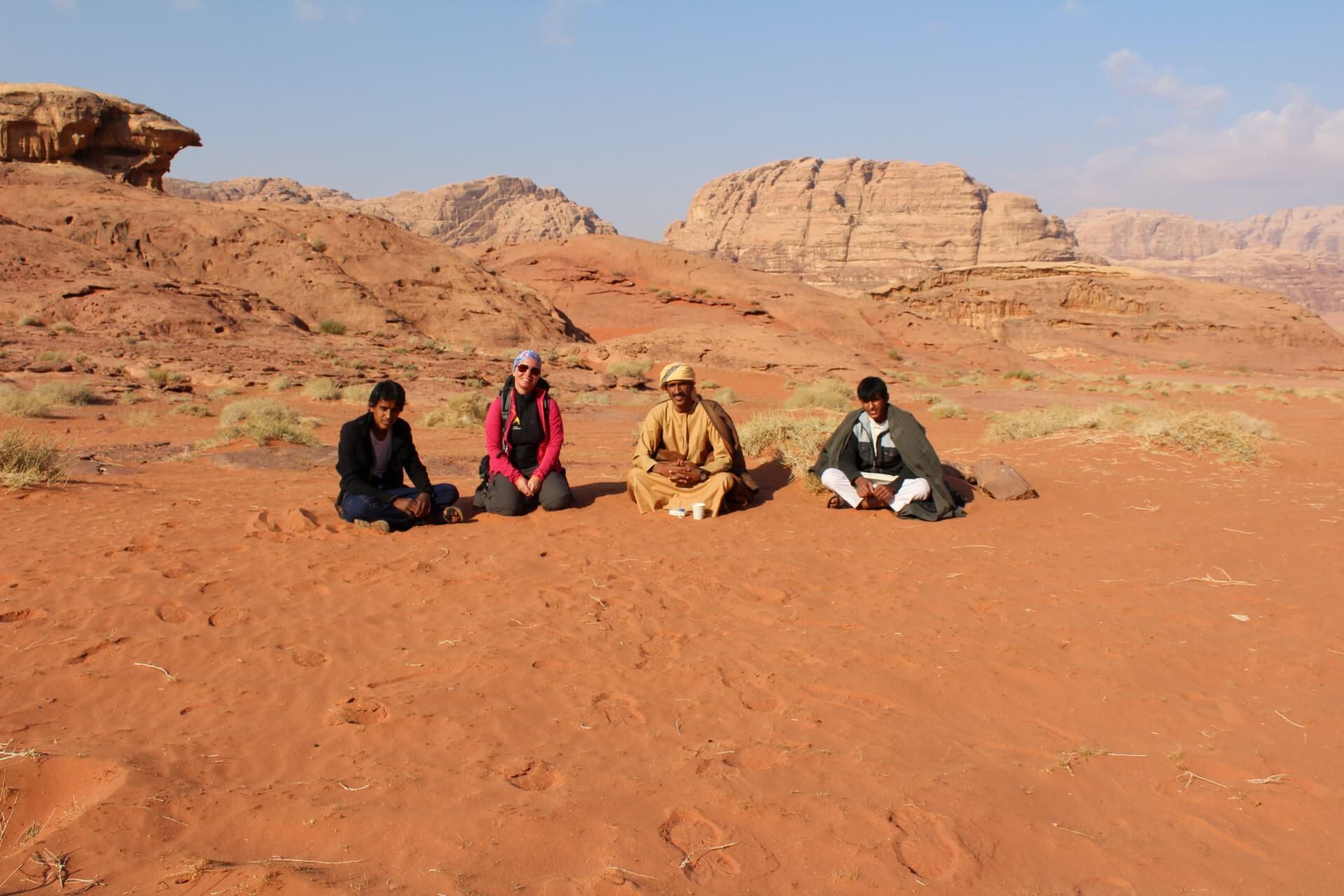 vier Menschen auf orangem Sand