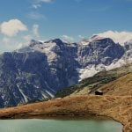 Ein kleiner See in alpiner Umgebung, bräunliches Gras herum. Schroffe Berge im Hintergrund