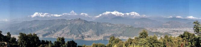 Panoramabild einer Bergkulisse unter blauem Himmel. Vor den Bergen liegt ein See.