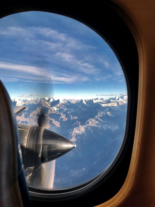 Blick aus Bullauge von Flugzeug auf teilweise schneebedeckte Berge. Blauer Himmel, wenige Wolken.