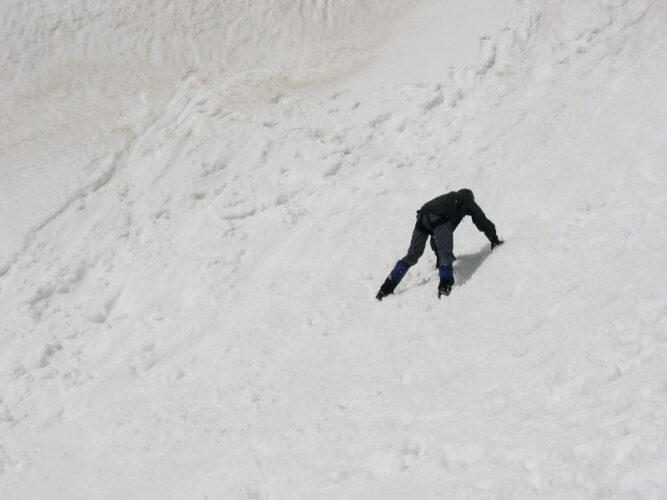 Mann in Liegestützhaltung auf einem Schneefeld.