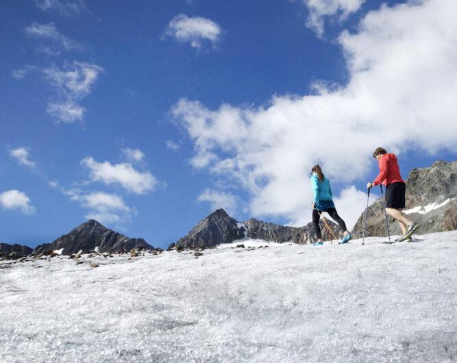 Zwei Bergsteiger auf einem Schneefeld. Die vordere Person in blauer, die hintere in roter Jacke. Blauer Himmel