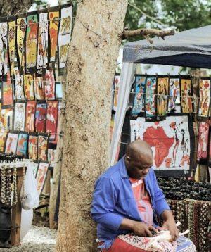 Künstler mit Holzgiraffe, Arts Center Südafrika