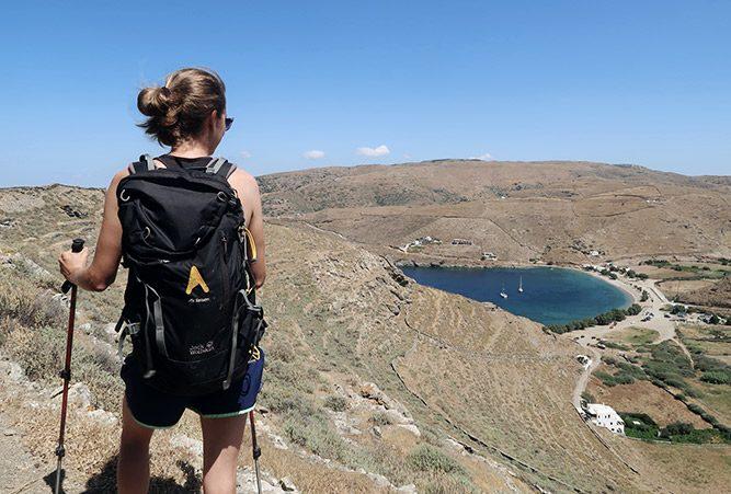 Wanderin von hinten, blickt hinunter auf einen See. Hügeliges Gelände