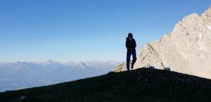 Eine Person auf einer ANhöhe, blauer Himmel im Hintergrund und letzte Sonnenstrahlen auf Bergen