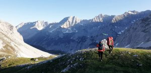 Bergkulisse mit Nachmittagssonne, Wanderer mit roten Jacken auf rechter Seite