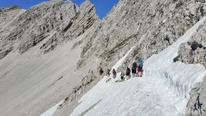 Sieben Personen an einem steilen Felshang gehen über ein Schneefeld