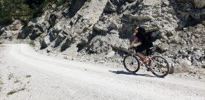 Person auf Fahrrad auf einem Schotterweg