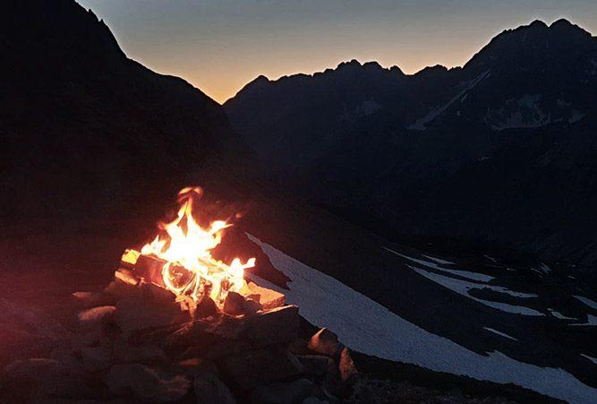 Bergsonnwend Feuer vor dunklen Bergen, Abend