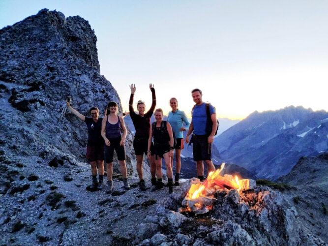 Sechs Personen auf einem Berg, vor ihnen ein Feuer. Abend