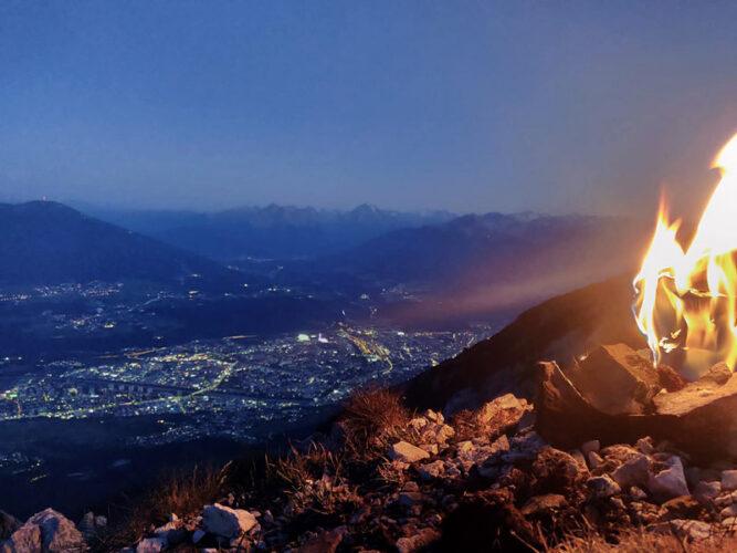 Feuer im rechten Teil des Bildes, Abend und Blick auf die Lichter einer Stadt im Tal
