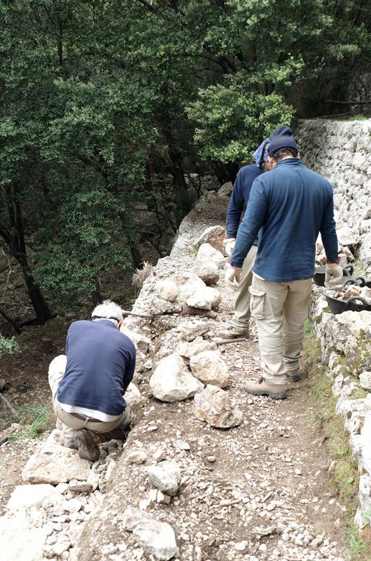Zwei Wanderer an einer steilen Stelle neben einer Trockensteinmauer