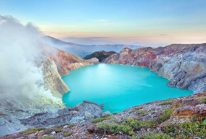 Ein türkisfarbener Kratersee am Fuße des Vulkans mit der blauen Lava.