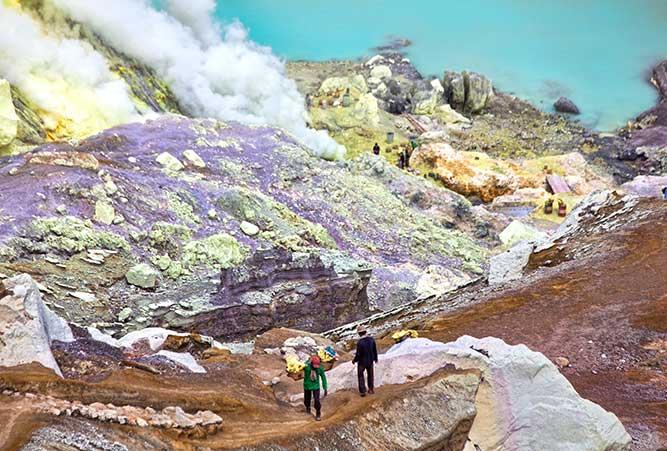 Zwei Männer tragen Körbe voller Schwefe von einer Mine aus auf einen Berg.