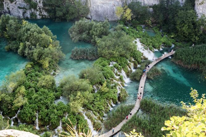 Eine geschwungene Holzbrücke auf türkisen Seen, grüne Bäume