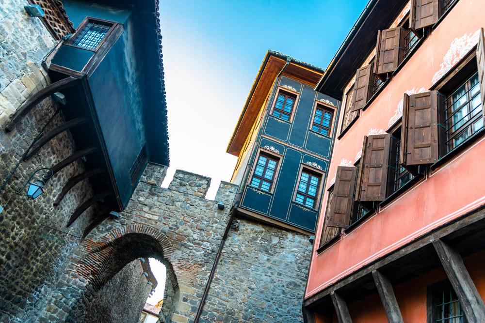 blick nach schräg oben auf stadtmauer und bunte häuserfassaden
