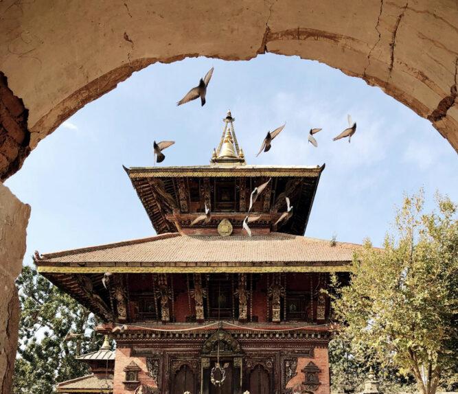 Blick durch einen Torbogen auf einen Tempel. Tauben fliegen in der Luft.