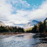 Ein See, Wald und Berge im Hintergrund, Glacier Nationalpark, USA. © Colin Maynard