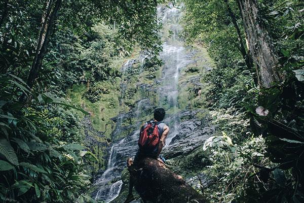 Wanderer vor einem Wasserfall in Costa Rica