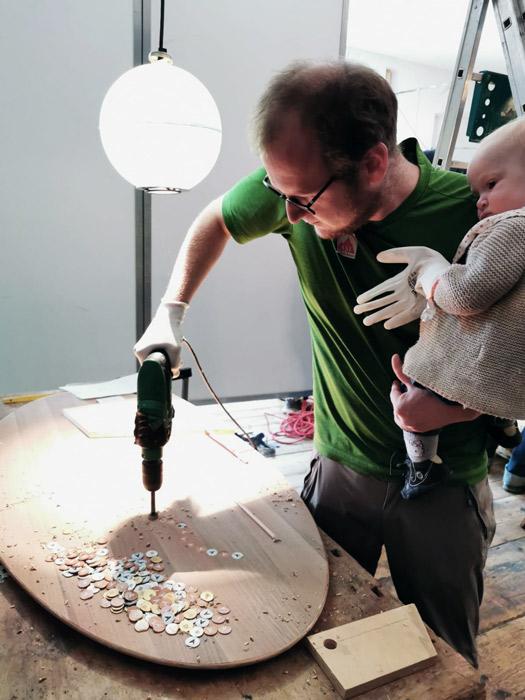 Mann in grünem Shirt bohrt in eine runde Tischplatte. er hält dabei ein Baby auf dem Arm. Im Hintergrund ist eine runde Lampe
