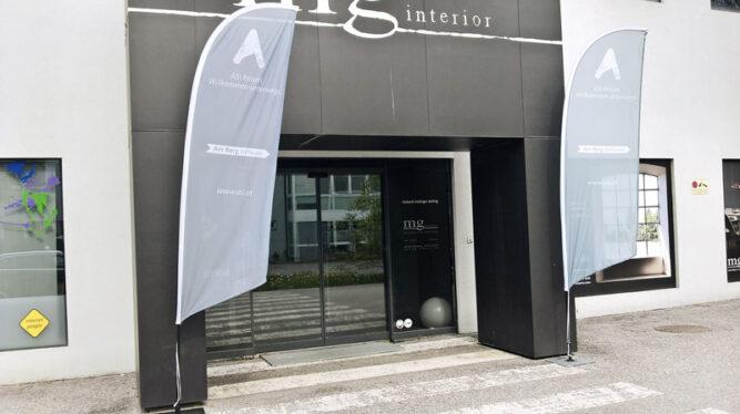 Breiter Eingangsbereich mit Schiebetüren. Segelflaggen links und recht aufgestellt mit dem ASI Firmenlogo