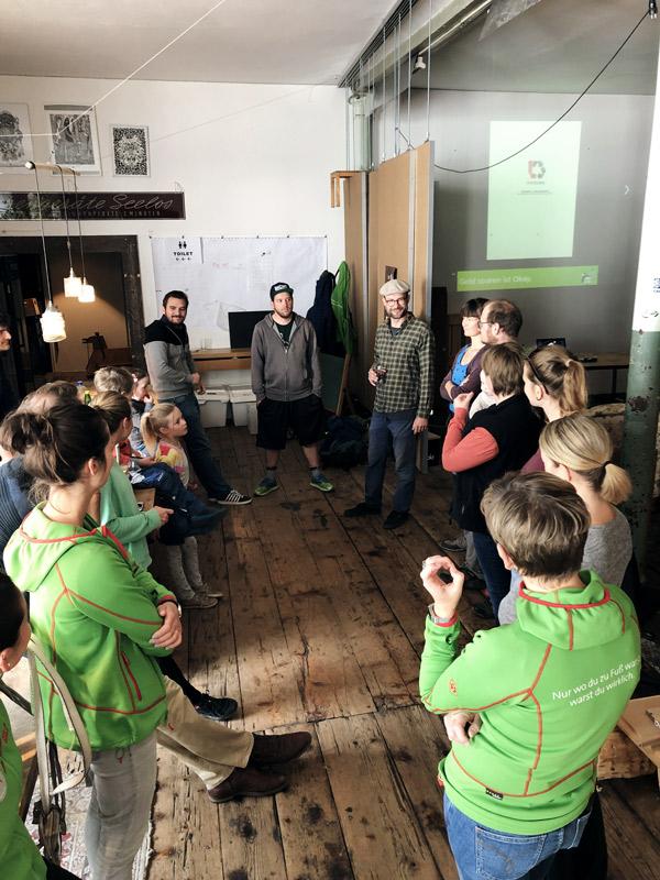 Eine Gruppe von Menschen steht im Kreis in einem hohen Raum